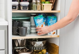person putting Almond Breze Shelf Stable in pantry